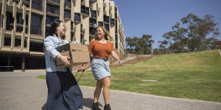 Two female students walking outside student accommodation, one holding a box.