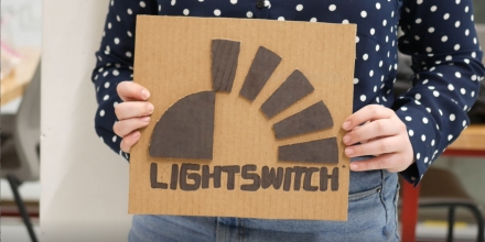 student holds carboard sign saying Lightswitch