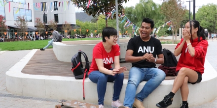 three students sit in the centre of campus laughing together
